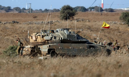 An Israeli soldier jumps off a tank in the Israeli-controlled Golan Heights, near the Israel-Syria frontier.