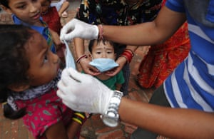 A volunteer provides free face masks to children who have come to see Machindranath chariot festival, which was postponed at the last minute as a precaution against the spread of coronavirus in Lalitpur, Nepal, on Saturday, 25 July, 2020.