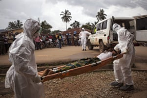 Healthcare workers load a man suspected of suffering from the Ebola virus in to an ambulance in Kenema, Sierra Leone.