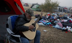 Camp fire evacuee Kelly Boyer plays guitar in front of his tent next to a Walmart parking in Chico, California.