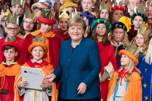 Berlin, Germany. Angela Merkel attends a welcome reception for carol singers. Children dressed as the Magi traditionally visit the German chancellor while they collect donations for charity