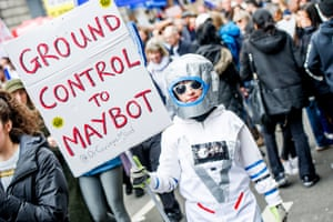 Protester in astronaut costume carries placard: 'Ground control to Maybot'