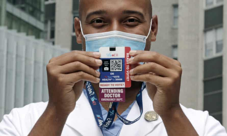Alister Martin, an emergency room doctor at Massachusetts General Hospital, holds up a voter information card he wears on his ID.