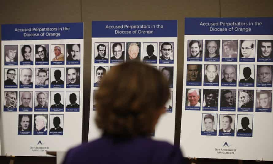 An advocate and survivor of sexual abuse looks at photos of Catholic priests accused of sexual misconduct by victims during a news conference in Orange, California, on 6 December 2018.