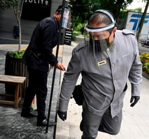 An employee sanitises his colleague before entering the restaurant they work in at Polanco neighbourhood in Mexico City on 7 July 2020 amid the new coronavirus pandemic.