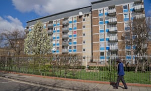 A man walks past a run-down council housing estate in east London