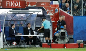 The referee, Milorad Mazic, watches a video review of a challenge by Chile's Gonzalo Jara on Germany's Timo Werner in the Confederations Cup final.