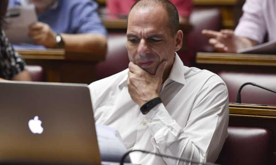 Yianis Varoufakis reads a document during a meeting at the Greek parliament in Athens.