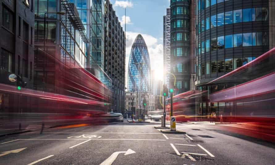 Double-decker buses drive through London's financial district