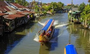 Boats navigate Khlong (Canal) Bang Luang in Bangkok