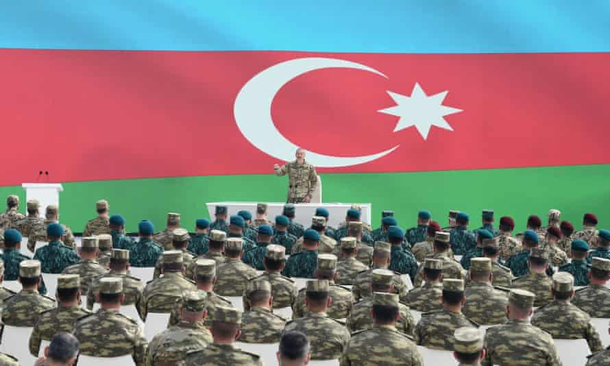 aliyev speaks with soldiers in front of flag