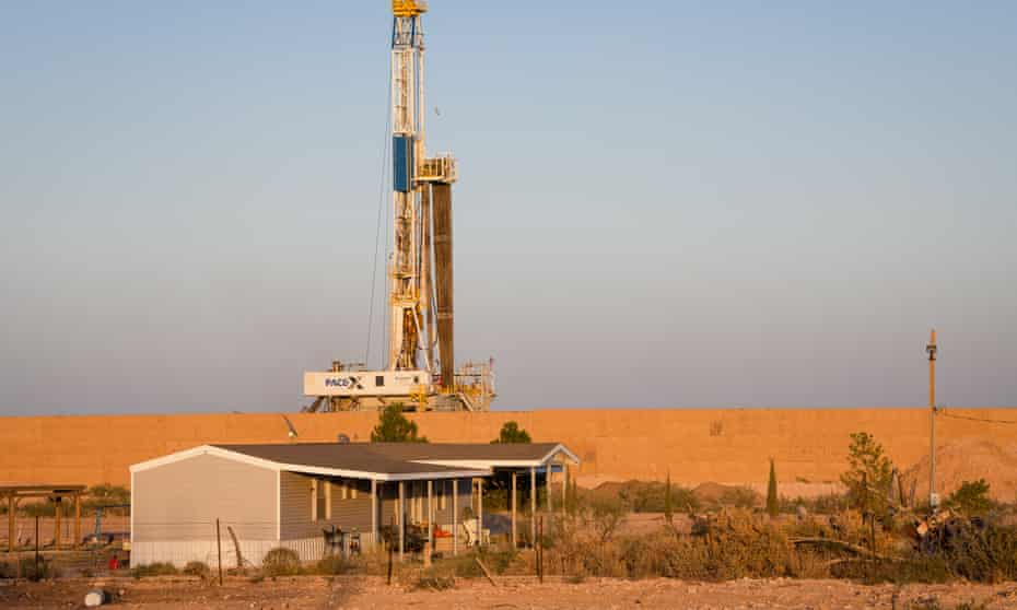 An oil drilling rig looms over a house in Eddy county, New Mexico.