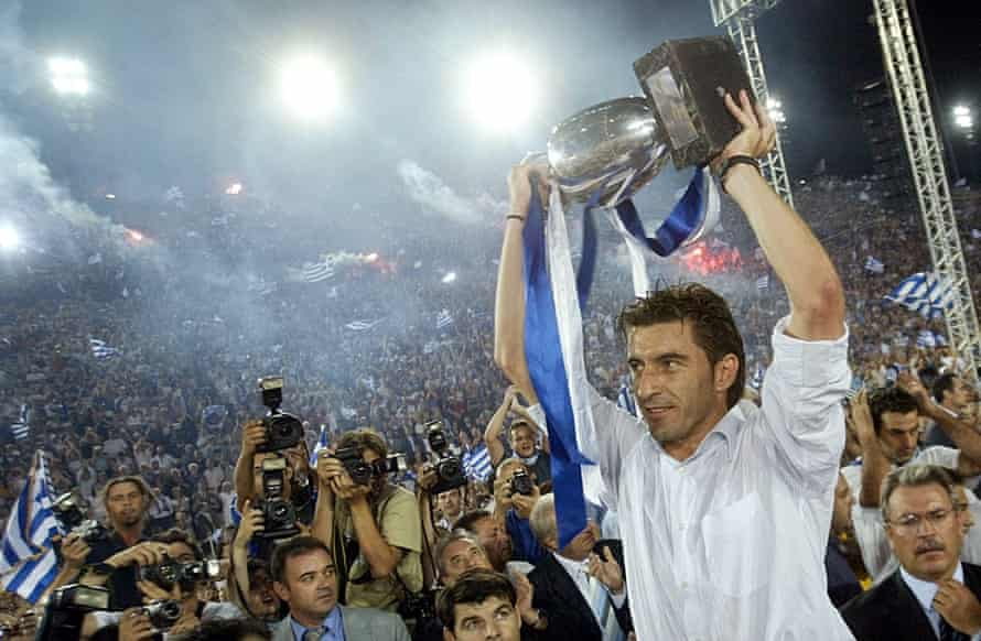 Greeks Salute The Return Of Their Victorious Football Team, led by their captain Theodoros Zagorakis as he raises the trophy during a victory fiesta at the Panathenaic Stadium in Athens, as thousands of Greeks welcomed the new UEFA Euro 2004 Champions.