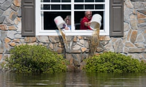 A couple pours water from Hurricane Florence out of their flooded home in Longs, South Carolina, on 20 September.