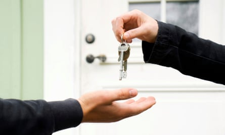 Hand drops house keys into someone else's hand