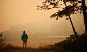 A person looks at a town by the Pacific Ocean coast as smoke from wildfires covers an area near Yachats, Oregon, on Tuesday.