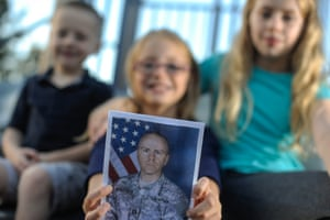 The children of Captain Michael Jackson, who is currently deployed from Fort Drum, hold up a photo of their father.