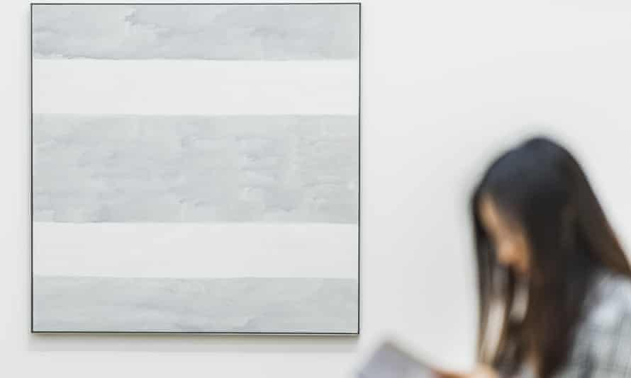 A viewer next to Agnes Martin's final painting Untitled 2004, at Tate Modern in London.