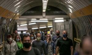 People wearing face masks walk at a metro station in Prague, Czech Republic.