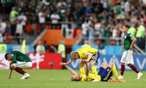 Emil Forsberg of Sweden celebrates victory with teammate Ola Toivonen whilst the Mexicans look disappointed.