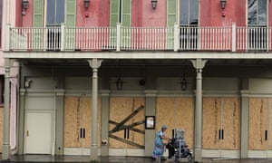 A woman pushes a stroller past a boarded up building in the French Quarter after Hurricane Ida knocked out power to the city