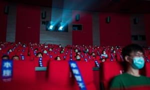 """Audiences wear masks and next to """"seats unavailable temporarily"""" signs in a cinema during a screening at Shanghai Film Centre in China. The 23rd edition of Shanghai International Film Festival will be held both offline and online in a bid to minimise the risk of virus spread, from 25 July to 2 August. Venues will be restricted to 30% capacity."""
