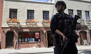 An armed police officer stands guard outside the Stonewall Inn, in New York.