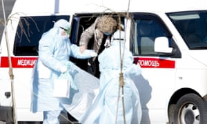 Paramedics, wearing protective suits and carrying suspected coronavirus patients, are seen near an ambulance as they arrived at the Kommunarka Hospital in Moscow, Russia.