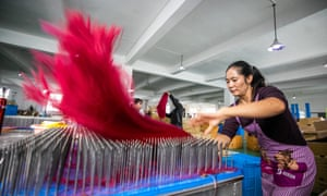 Employees work on the production line of a wigs factory at Hanya Arts & Crafts Co in Hezhang County