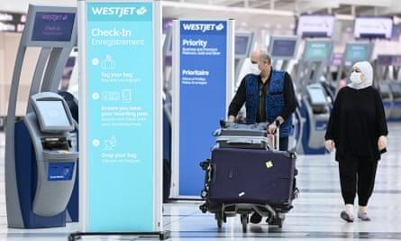 Passengers wearing masks navigate Pearson international airport in Toronto