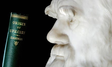 A copy of Darwin's book the Origin of Species is pictured in front of a lifesize stone bust of the naturalist