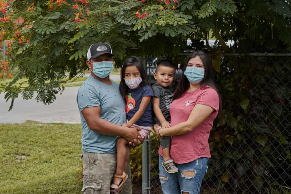 Elbin Sales Pérez, 31, a farmworker and landscaper, poses outside his home with his wife, Yecenia Solorzano, and their two children.