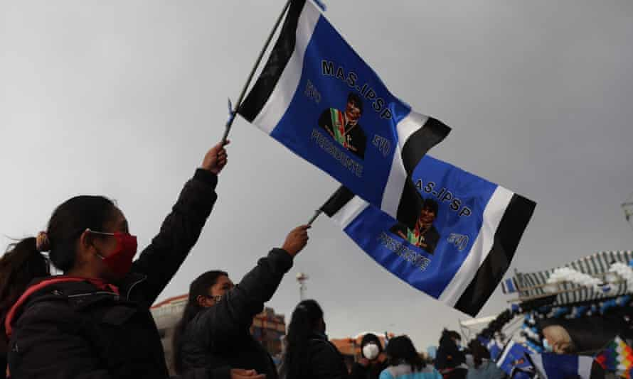 Supporters of Luis Arce hold flags with an image of Evo Morales