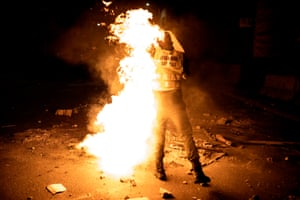 Dakar, Senegal. A Senegalese police officer gets covered in flames as he tries to put out a fire after protests erupted during a curfew. The Senegalese president, Macky Sall, announced the state of emergency with a night curfew for two regions, including Dakar, to stop the rise of the coronavirus