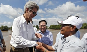 John Kerry shakes hands with Vo Ban Tam at the spot on Bay Hap river where they fought nearly 50 years ago.