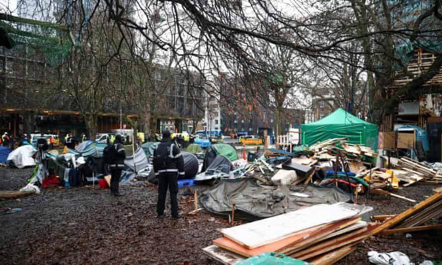Enforcement agents watch over a makeshift camp where Extinction Rebellion activists demonstrate as others occupy tunnels under Euston Square Gardens