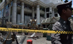 A Bangkok police officer inspects the cordoned-off site of a bomb blast at the popular Erawan shrine in the heart of city's tourist and commercial centre.