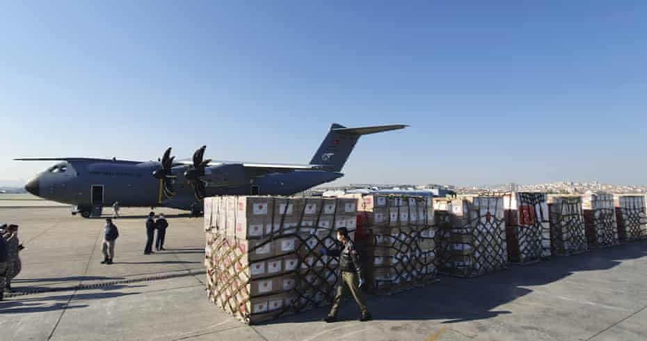 Soldiers prepare to load a military cargo plane with personal protective equipment donated by Turkey to help the US