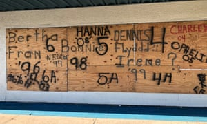 Redix clothing store is boarded up with the names of past hurricanes: Bertha, Fran, Matthew and Irene.