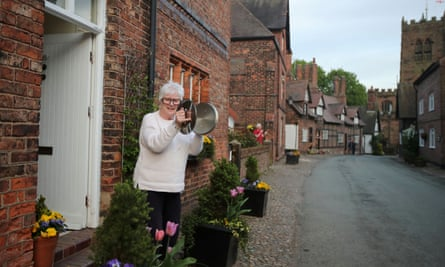 A local resident in Great Budworth use pot lids to applaud from her doorstep during the Clap for our Carers campaign in support of the NHS