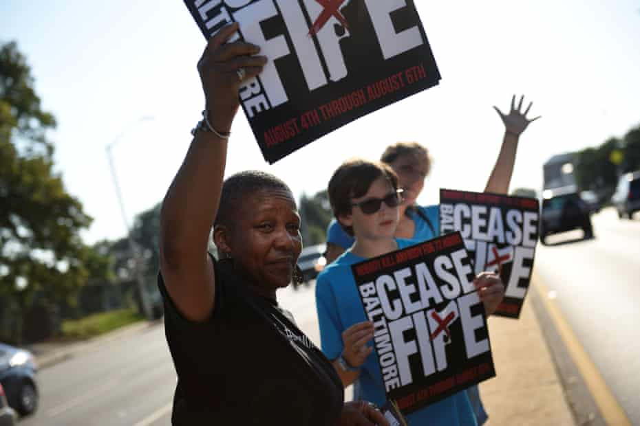 People hold signs during the first 72 hour community-led Baltimore Ceasefire last August.