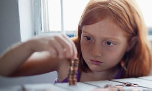 A girl stacking coins at a table