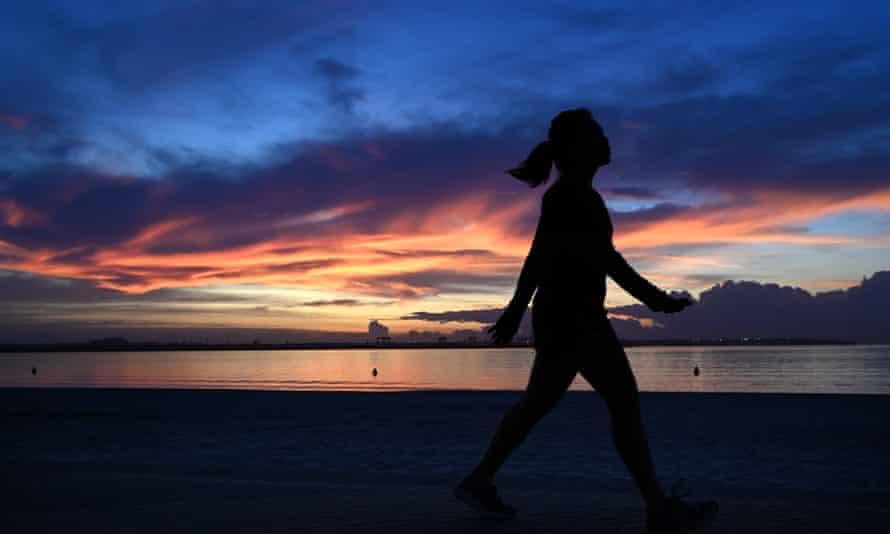 Woman walks at sunrise