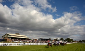 Horses pass the packed grandstand at the reopened Hereford racecourse