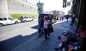 A couple walk past a homeless person outside Windsor Castle