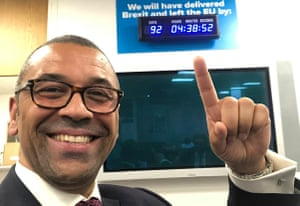 Tory party chairman James Cleverly points cheerily at the newly installed Armageddon Clock in Conservative HQ.