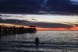 Adelaide, AustraliaA surfer watches the sunset over Grange beach in Adelaide