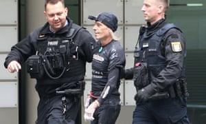 Police officers escort Robert away after his descent.
