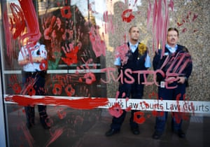 Security staff stand behind the supreme court windows covered in red ochre after a protest over the death of Elijah Doughty.