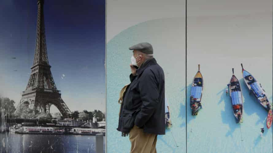 A man wearing a face mask walks by a closed travel agency in Lisbon.